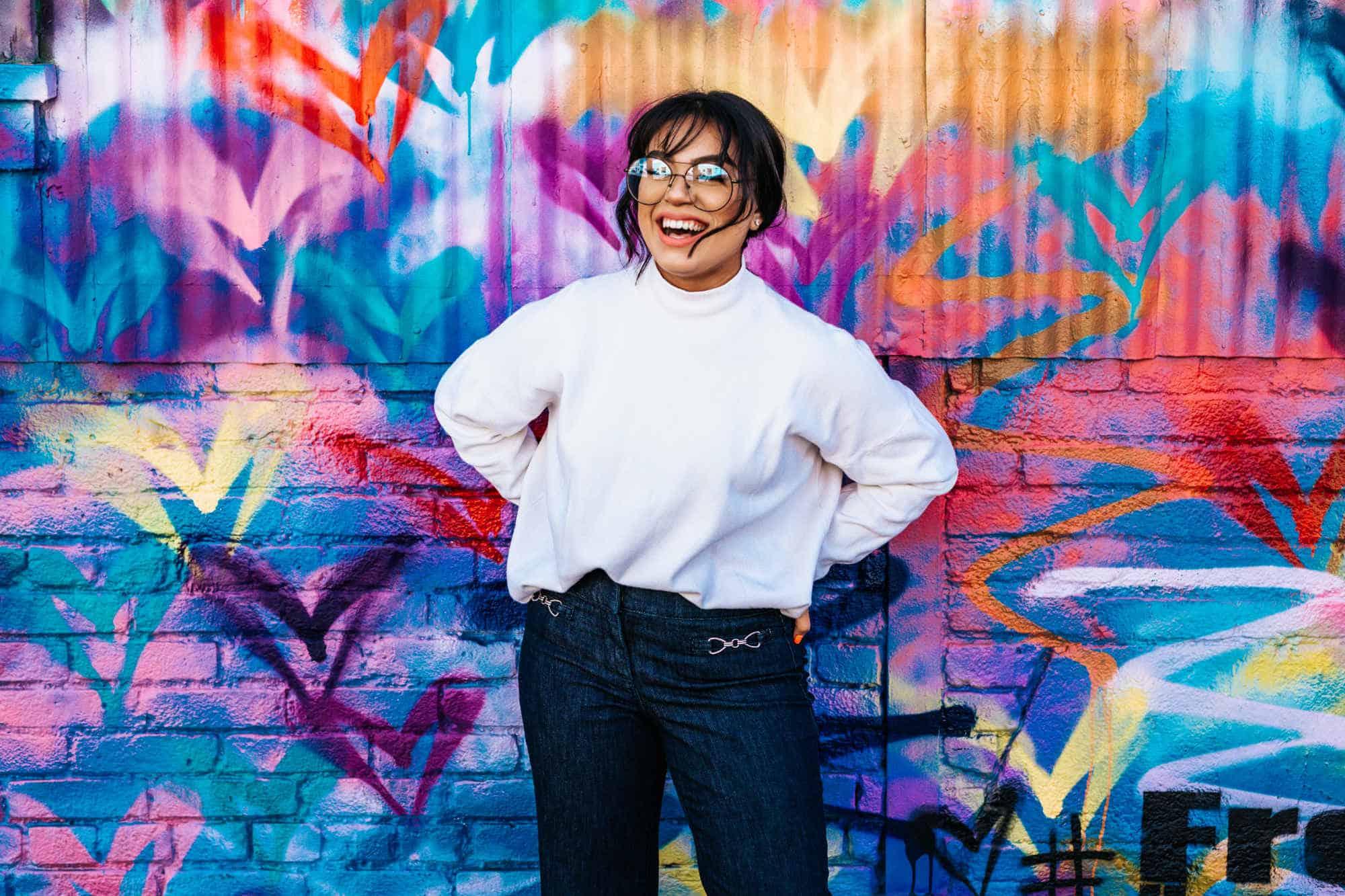 Lachende junge Frau vor Graffiti Wand