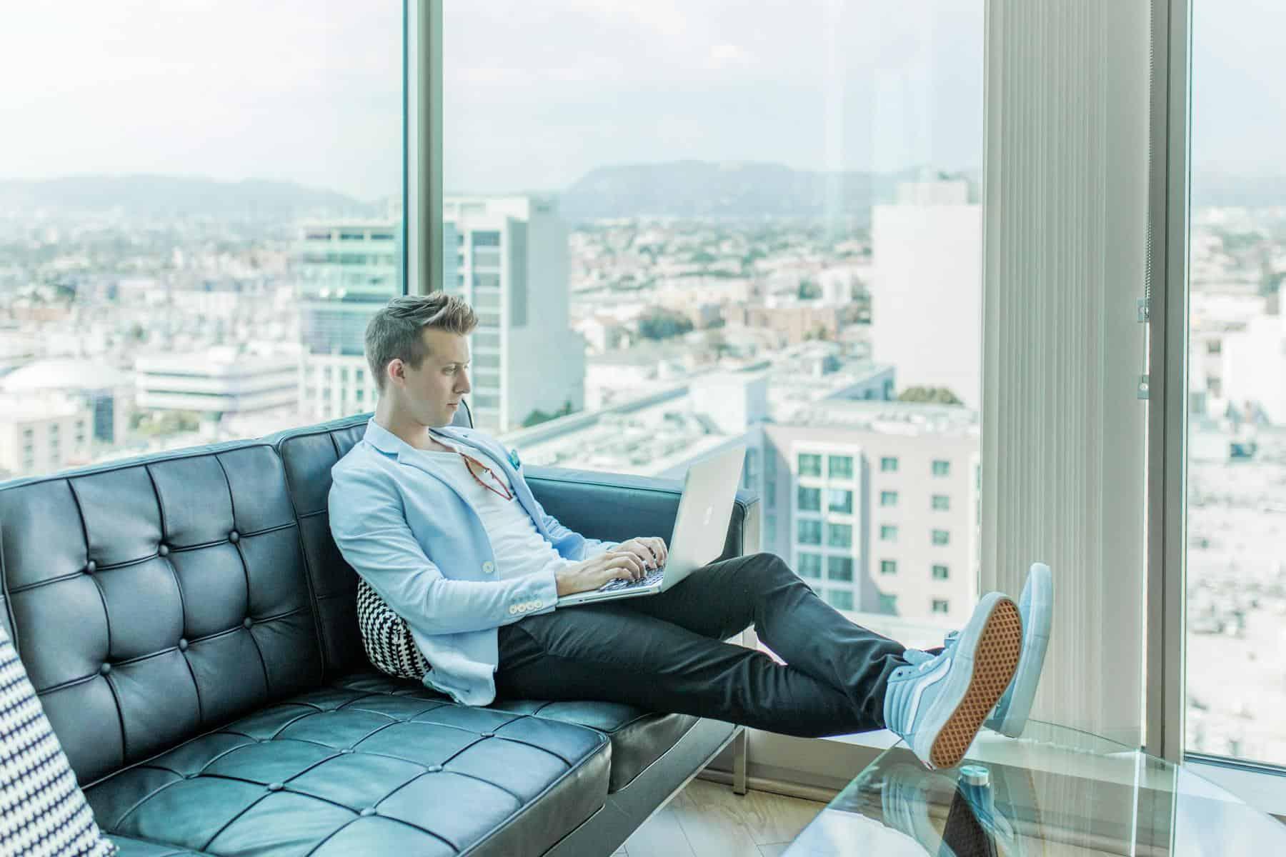 Das Foto zeigt einen jungen Mann der gerade remote mit seinem Notebook arbeitet.
